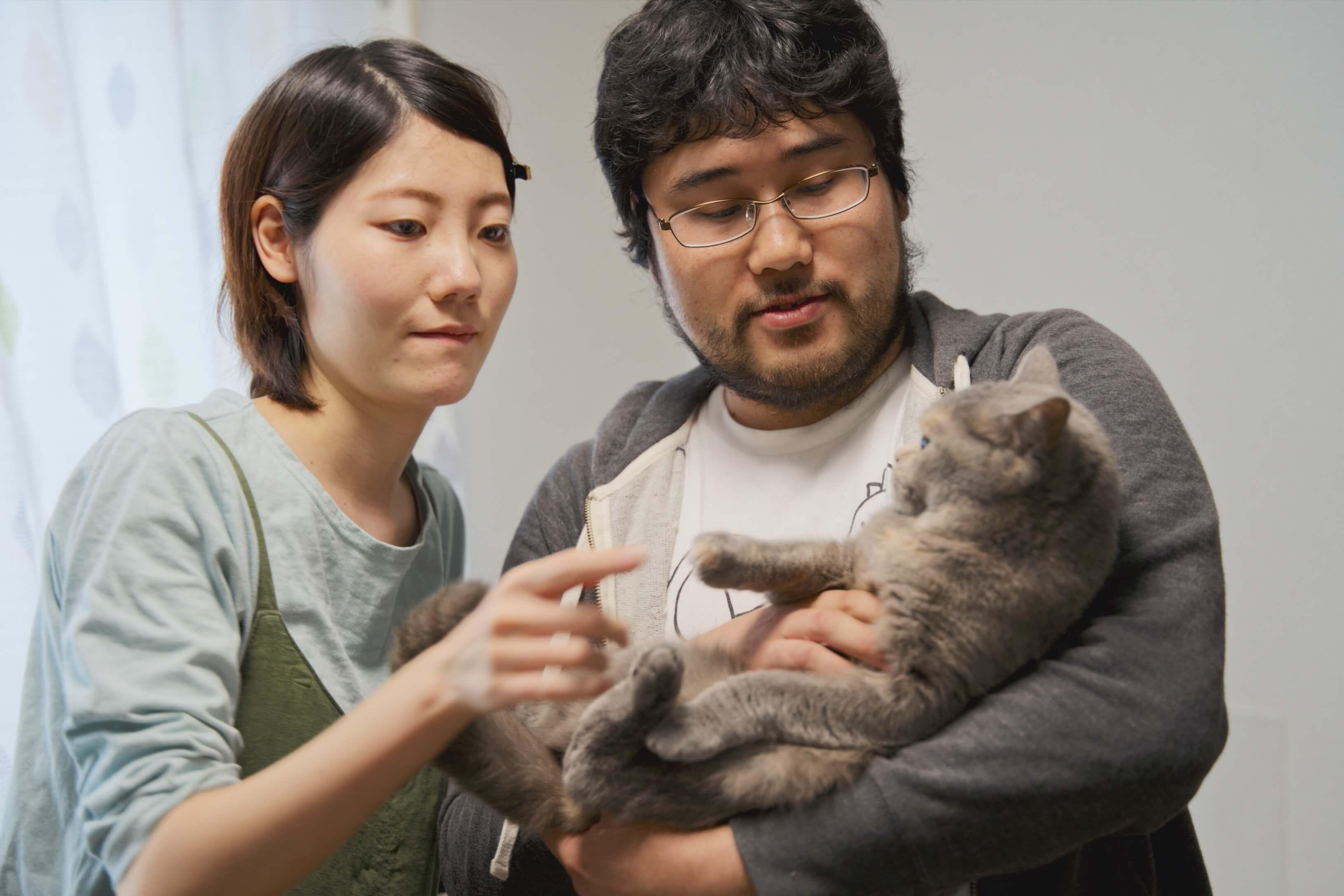 猫をあやすペアーズ夫婦のKeitaroさん・Mayuriさんの写真