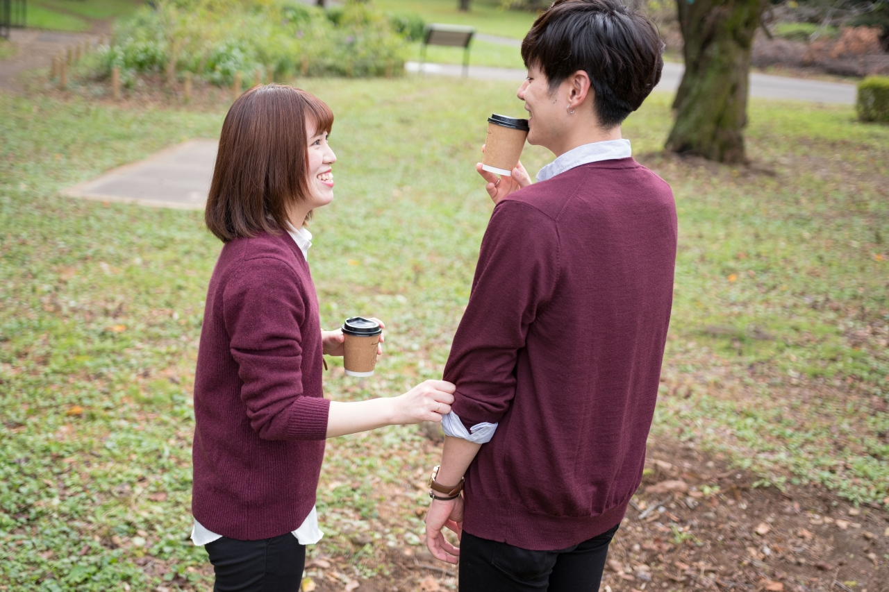 公園でコーヒーを飲むカップル