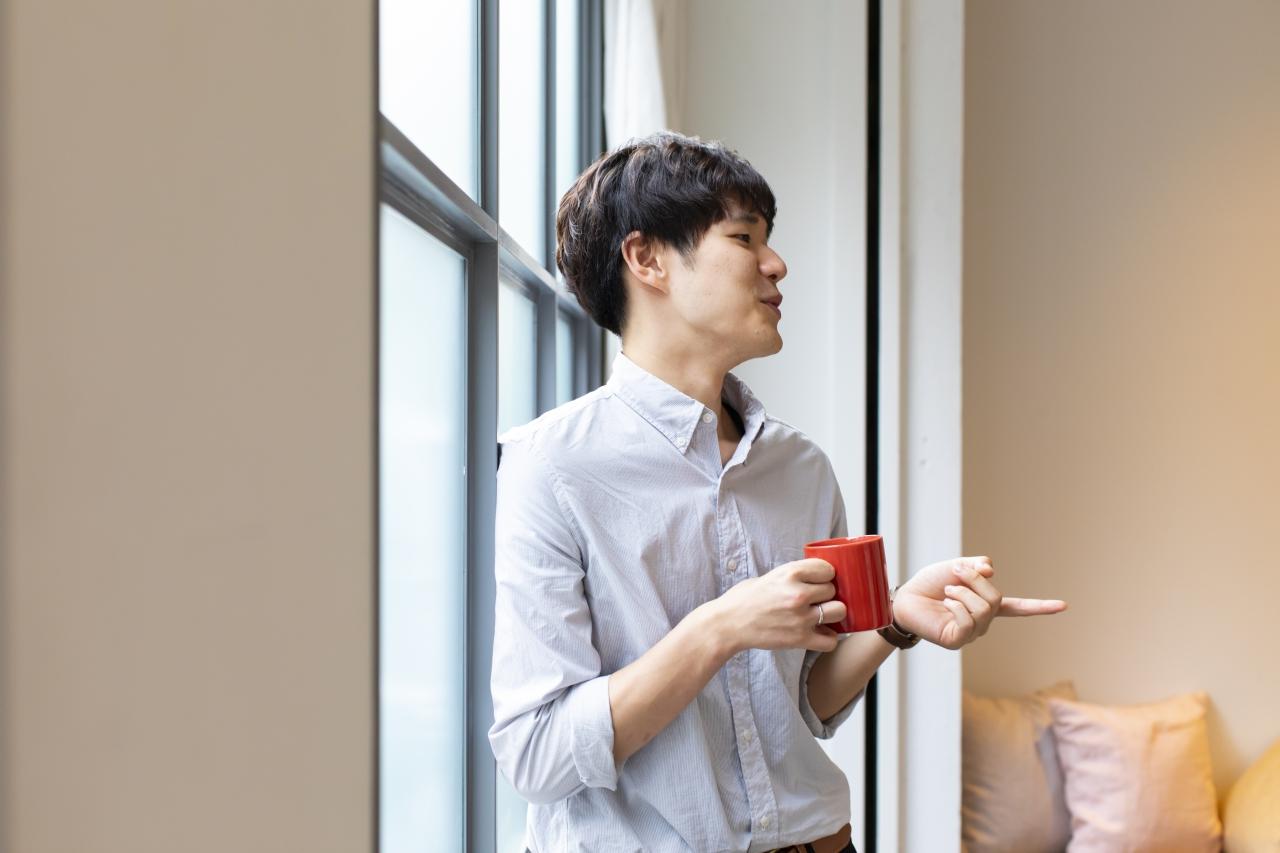 窓際でコーヒーを飲んでいるTakuhikoさん